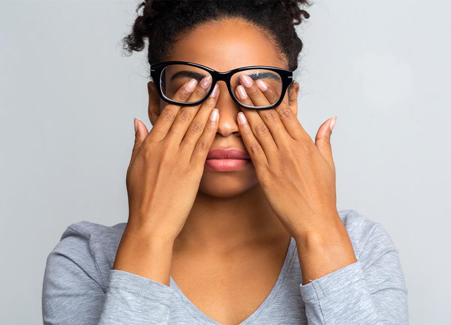 woman in glasses rubs her eyes, experiencing dry eyes